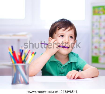 Little boy is drawing on white paper using color pencils - stock photo