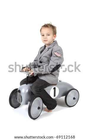Little boy is driving a toy vehicle - stock photo