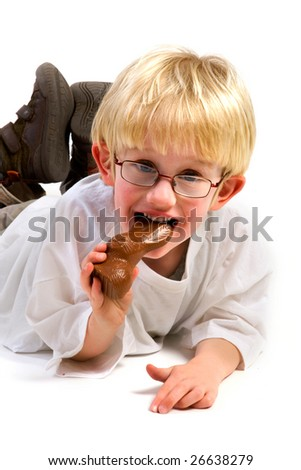 Little boy is eating a chocolate easter hare - stock photo