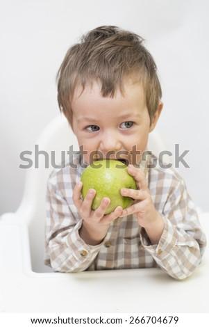 Little boy is eating green apple - stock photo