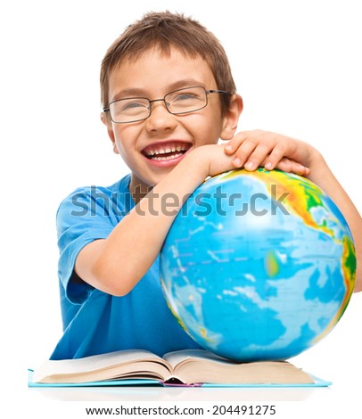 Little boy is examining globe while sitting at table, isolated over white - stock photo
