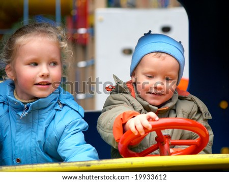 Little boy is learning to drive on the pleasure-ground and his sister
