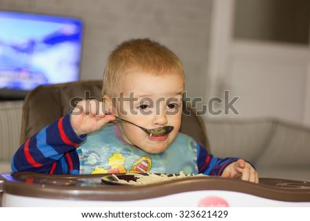 Little boy is learning to eat by himself using a spoon (shallow DOF). - stock photo