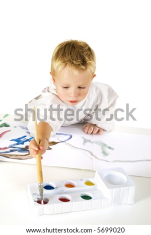 Little boy is making a painting with colored paint - stock photo