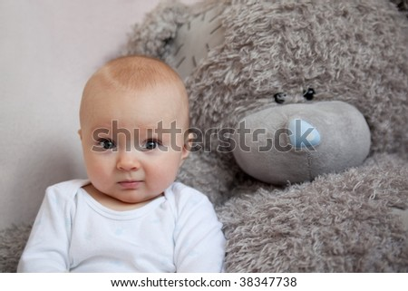 Little boy is on sofa together favorite teddy - stock photo