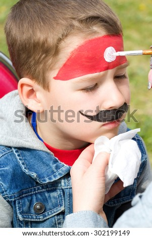 little boy is painted with watercolors - stock photo