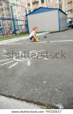 Little boy is playing with cars outdoors - stock photo