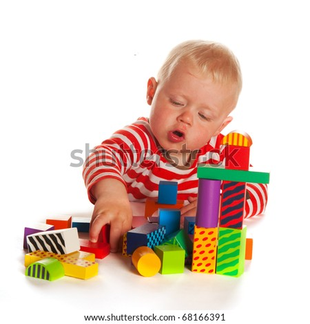 Little boy is playing with colorful blocks