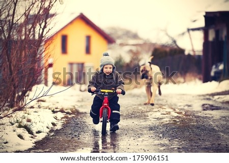 Little boy is playing with his dog on the street. - stock photo