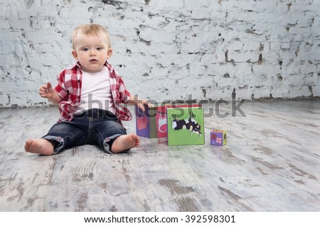little boy is playing with toy blocks