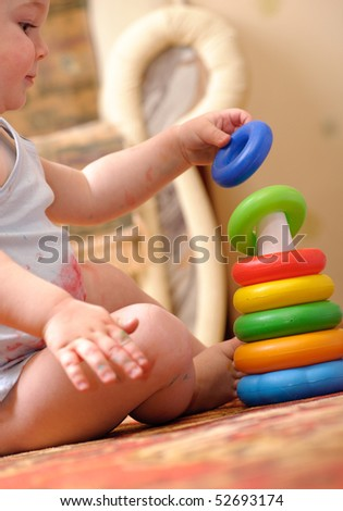 Little boy is playing with toy pyramid - stock photo