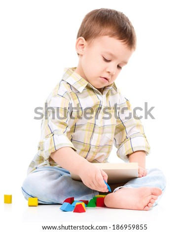 Little boy is playing with toys, isolated over white - stock photo