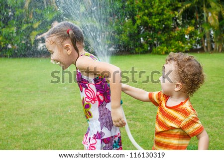 little boy is pouring a water from a hose at her sister - stock photo