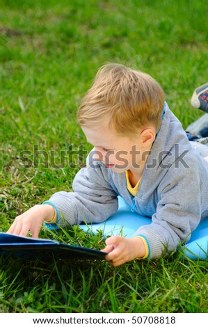 Little boy is reading a book outdoor