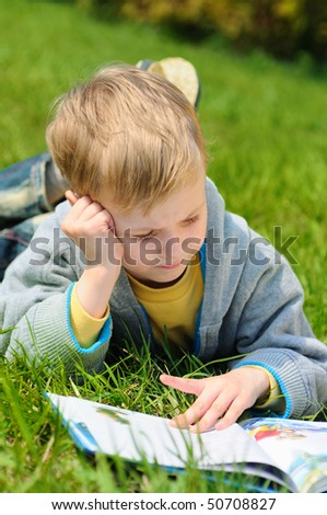 Little boy is reading a book outdoor - stock photo