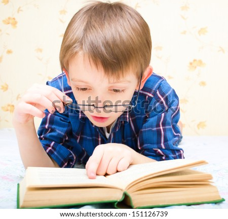 Little boy is reading a book while laying on bed and wearing glasses - stock photo