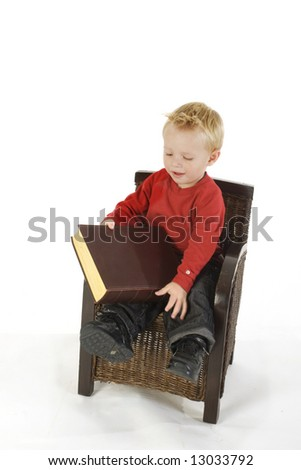 Little boy is reading a very thick book