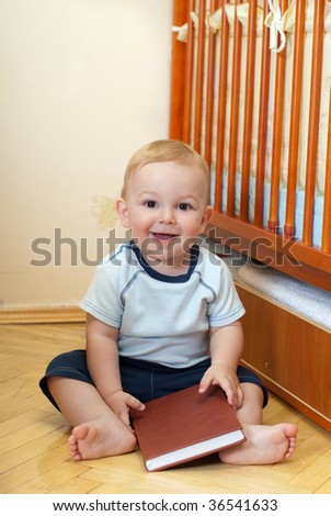 Little boy is reading book near his bed - stock photo