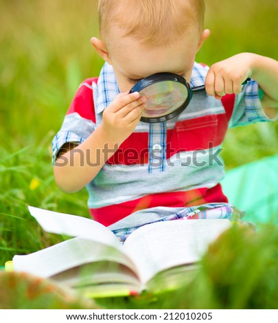 Little boy is reading book using magnifier while sitting on green grass outdoors - stock photo
