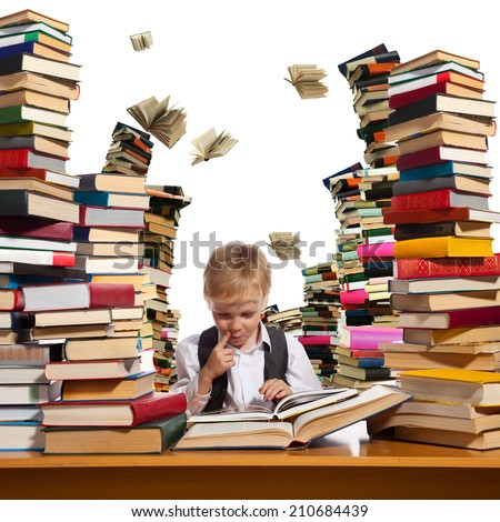 Little boy is reading interesting book. High stacks of books are on the table near him. - stock photo