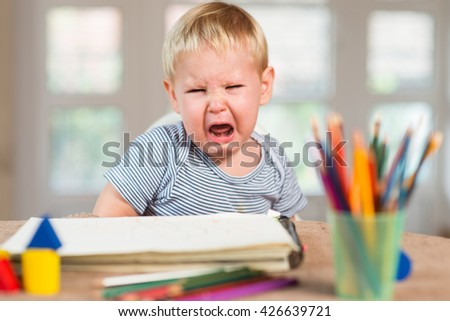 Little boy is seating at table and crying - stock photo