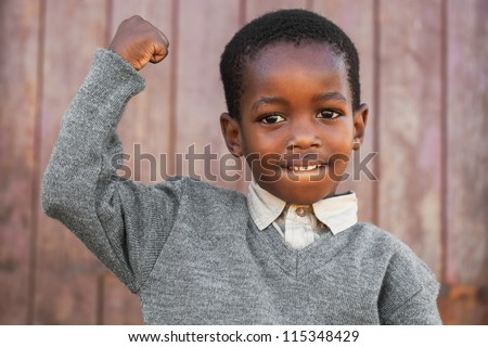 Little boy is showing off his muscles to the photographer.