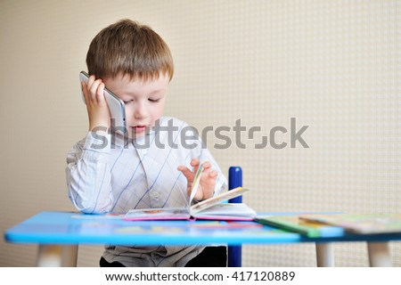little boy is sitting at a desk in school and speaking on the phone - stock photo