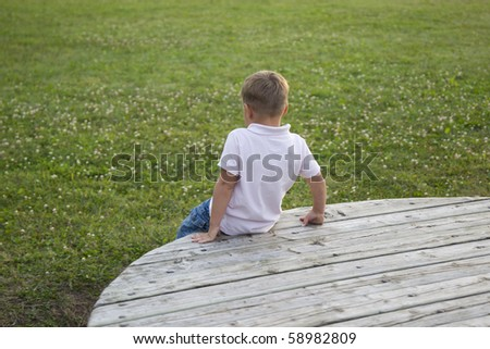 Little boy is sitting bored on a wooden board