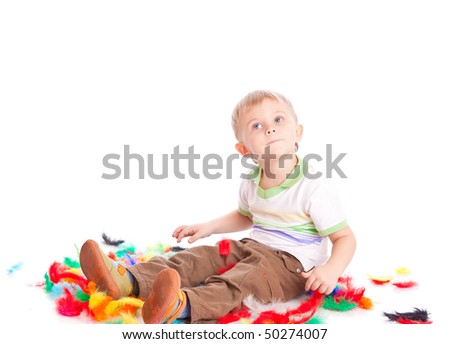 Little boy is sitting on a flow with feathers. Isolated on white background