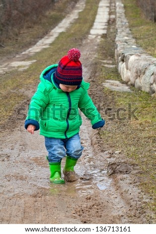 little boy is standing in a puddle