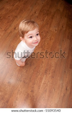 Little boy is standing on brown floor. Place for text. - stock photo