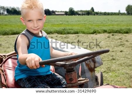 Little boy is steering a tractor.
