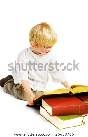 Little boy is studying in very thick books - stock photo
