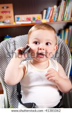 Little boy is talking via mobile phone - stock photo