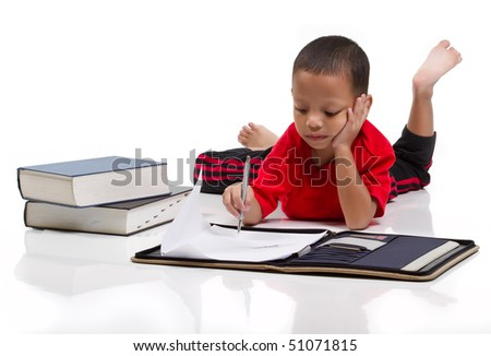 Little boy is thinking while drawing on paper - stock photo