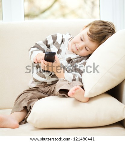 Little boy is watching tv while sitting on a couch - stock photo