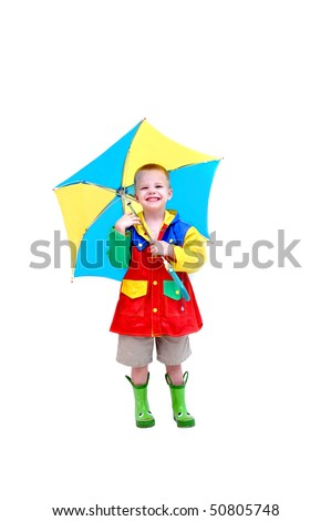 Little boy is wearing a raincoat, rubber boots and holding a brightly colored umbrella.  He has a funny expression on his face as if he is laughing at himself for thinking it might rain. - stock photo