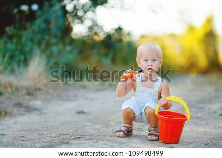 Little boy iwith bucket n summer outdoor - stock photo