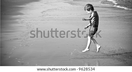 little boy jumping and splashing on the beach, black and white - stock photo