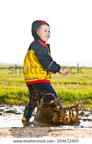 Little boy jumping in a mud puddle - stock photo