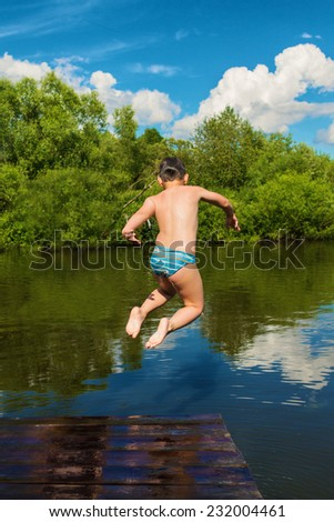 Little boy jumping into a river - stock photo