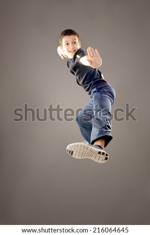 little boy jumping isolated in grey background  - stock photo