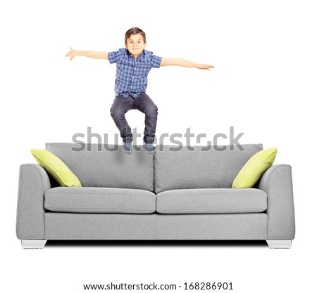 Little boy jumping on a sofa isolated on white background - stock photo