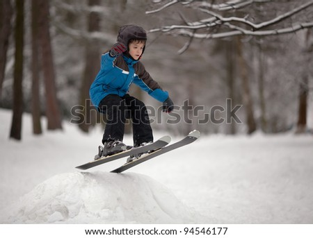 Little boy jumping on downhill skis - stock photo