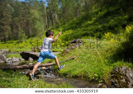 Little boy jumps over a stream in a forest