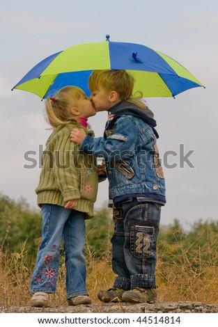 Little boy kiss girl, under umbrella in autumn day - stock photo