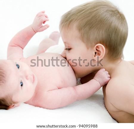 Little boy kiss her newborn sister - stock photo