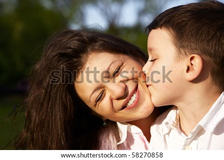 little boy kiss his mother outdoor - stock photo