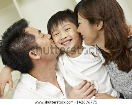 little boy kissed by mother and father. - stock photo