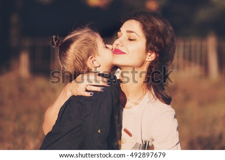 Little boy kisses his mother in a cheek.They standing in the field on the sunset